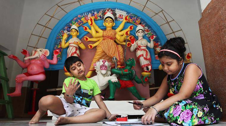 Young ones of the Daw family play in front of the Durga idol at their Jorasanko residence. (Source: Express photo by Partha Paul)