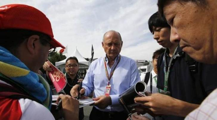 McLaren Formula One Executive Chairman Ron Dennis signs autographs as he arrives for the Japanese F1 Grand Prix at the Suzuka Circuit