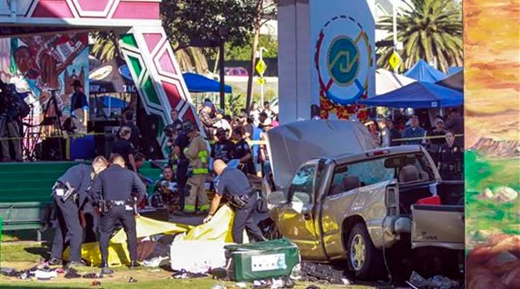Police cover the bodies of people that were killed when a pickup truck landed on them after it flew off a ramp to the San Diego Coronado Bridge as paramedics prepare to put an injured man on a gurney, background, at Chicano Park in San Diego on Saturday, Oct. 15, 2016. Four people were killed and nine were injured on Saturday after an out-of-control pickup truck plunged off the San Diego-Coronado Bridge and plowed into crowd gathered at a festival below, authorities said. (Hayne Palmour IV/The San Diego Union-Tribune via AP)