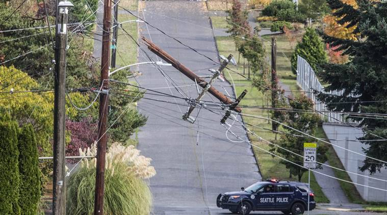 Seattle Police watch over a snapped power pole from downed trees sitting across SW Hinds Street and 47th Ave. SW, Friday, Oct. 14, 2016 in Seattle. Thousands of people were without power in Seattle as heavy rains and winds moved through the Pacific Northwest. (Steve Ringman/The Seattle Times via AP)