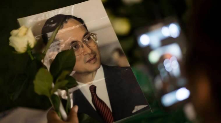 Thai mourner holds an archive portrait of Thai King Bhumibol Adulyadej before lighting candles outside Grand Palace in Bangkok, Thailand, Saturday, Oct. 15, 2016, as some thousands of Thai mourners thronged Saturday to the palace complex where King Bhumibol Adulyadej's body is being kept. The government has said a regent would be the caretaker of the monarchy until the crown prince takes over following his father's death. (Wason Wanichakorn)