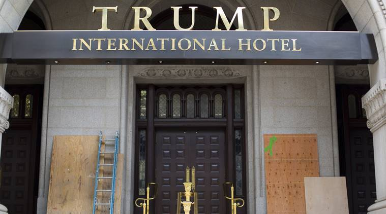 "Plywood covers up graffiti at the entrance to the Trump International Hotel, Sunday, Oct. 2, 2016, in Washington. District of Columbia police said someone spray-painted the phrases ""black lives matter"" and ""no justice no peace"" on the front of the building on Saturday afternoon. (AP Photo/Pablo Martinez Monsivais)"