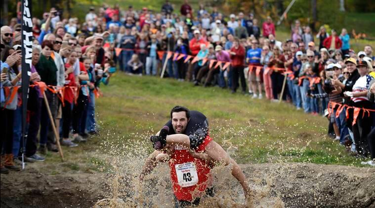 Elliot Storey races through the mud pit while carrying his wife, Giana Storey, both of Westbrook, Maine, to win the North American Wife Carrying Championship, Saturday, Oct. 8, 2016, at the Sunday River Ski Resort in Newry, Maine. They competed against 43 other couples to win today's 17th annual championship. They covered the 278-yard obstacle course in 59.18 seconds. (AP Photo/Robert F. Bukaty)