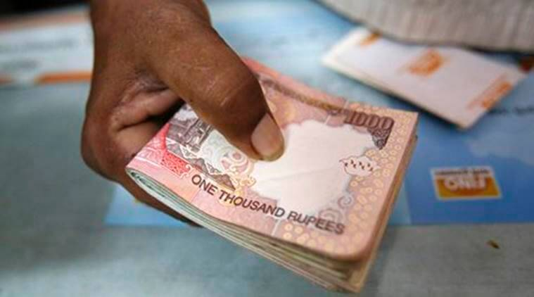 A customer hands a bundle of Indian Rupee currency notes to a teller at a financial institution in Mumbai July 2, 2013. Concerned about the rupee's fall to a record low, the Reserve Bank has discreetly phoned trading desks with unusually explicit messages to cut their speculative positions in the currency, said three senior market participants with direct knowledge of such calls. REUTERS/Vivek Prakash (INDIA - Tags: BUSINESS) - RTX119WQ