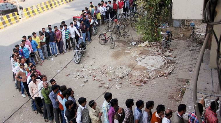 Gurugram : People stand in a long queue outside an ATM to withdraw money in Gurugram on Sunday. PTI Photo (PTI11_20_2016_000118B)
