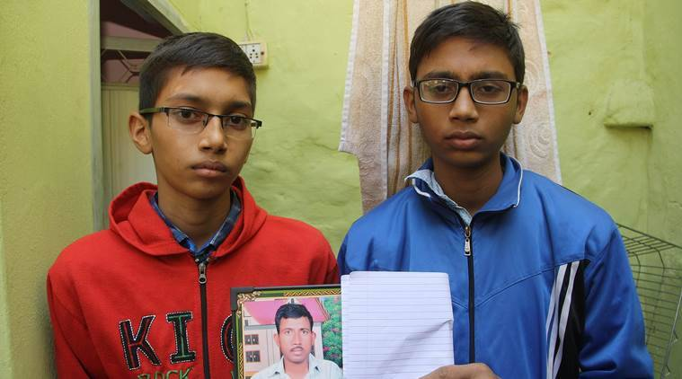 BSF Jawans sons Hitesh and Paras( red) holding their father's pic at home in Rohtak on Monday .November 21, 2016: Express Photo
