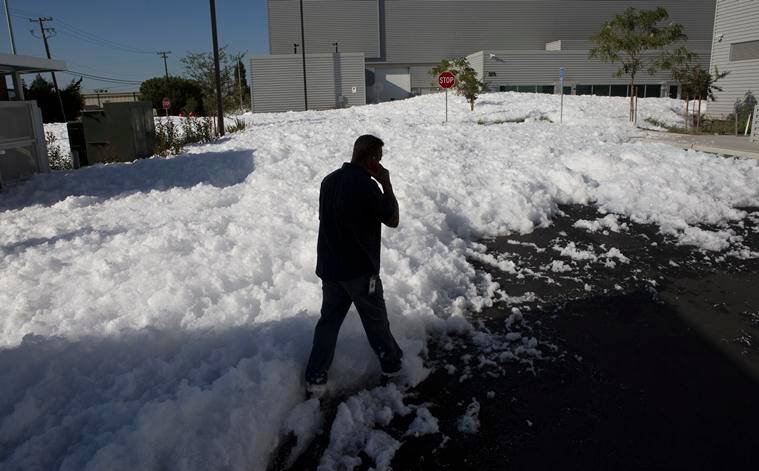 A man walks through chemical foam used as a fire retardant that spilled out at the back side of San Jose International Airport in San Jose, Calif., Friday, Nov. 18, 2016. A bobbing sea of white foam several feet deep in spots spewed out of a large hangar at the airport, covering cars and blocking businesses as it cascaded onto a nearby street. (Patrick Tehan/Bay Area News Group via AP)