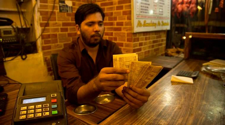 A man counts 500 rupee notes at a restaurant in New Delhi, India , Tuesday, Nov. 8, 2016. In a move to curb the flow of black money, Indian Prime Minister Narendra Modi announced Tuesday night that notes in the denomination of 500 and 1,000 will be void from midnight tonight. (AP Photo/ Anupam Nath)