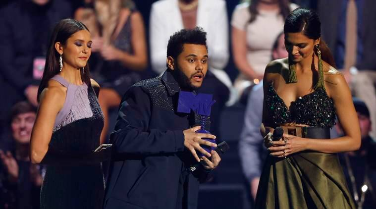 The Weeknd, centre, receives the Best Video Award from Nina Dobrev, left and Deepika Padukone, during the MTV European Music Awards 2016, in Rotterdam, Netherlands, Sunday, Nov. 6, 2016. (AP Photo/Peter Dejong)