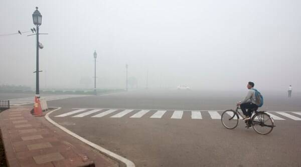 A cyclist rides on a road enveloped by smoke and smog, on the morning following Diwali festival in New Delhi, India, Monday, Oct. 31, 2016. As Indians wake Monday to smoke-filled skies from a weekend of festival fireworks for the Hindu holiday of Diwali, New Delhi's worst season for air pollution begins, with dire consequences. A new report from UNICEF says about a third of the 2 billion children in the world who are breathing toxic air live in northern India and neighboring countries, risking serious health effects including damage to their lungs, brains and other organs. (AP Photo/Manish Swarup)