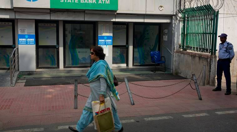 A woman walks past a closed ATM in New Delhi, India, Wednesday, Nov. 9, 2016. Indians awoke to confusion Wednesday after the government withdrew the highest-denomination currency notes overnight to halt money laundering in a country where many in the poor and middle-class still make day-to-day transactions in cash. (AP Photo/Manish Swarup)