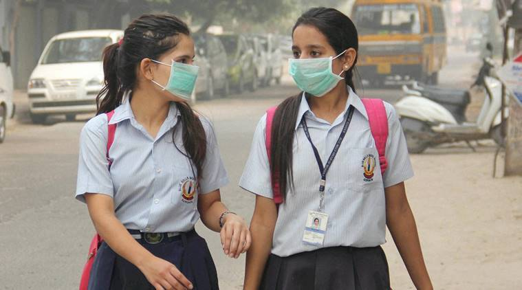 Gurgaon: School girls wearing anti-air pollution masks as protective gear after pollution reached hazardous levels in Gurgaon on Saturday. PTI Photo(PTI11_5_2016_000175A)