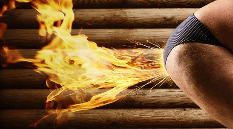 Very strange naked man farts by fire on the background of wooden wall