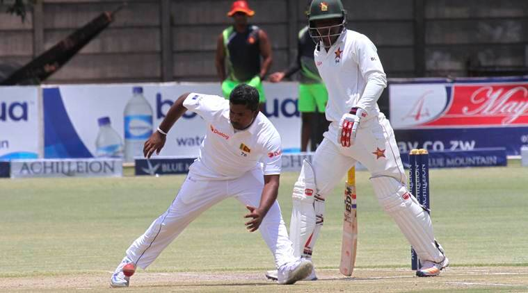 Sri Lanka captain Rangana Herath, left, goes for the ball as Zimbabwe batsman Brian Chari looks on during the test cricket match against Zimbabwe at Harare Sports Club in Harare, Tuesday, Nov, 8, 2016. Zimbabwe is playing host to Sri Lanka in a two test match encounter. (AP Photo/Tsvangirayi Mukwazhi)