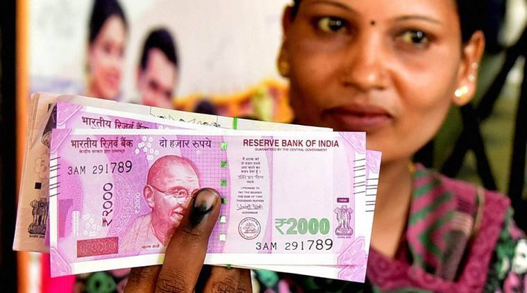 A lady display the currency notes and indelible ink after withdrawing the amount at the State Bank in Bengaluru on Wednesday. (PTI Photo by Shailendra Bhojak)
