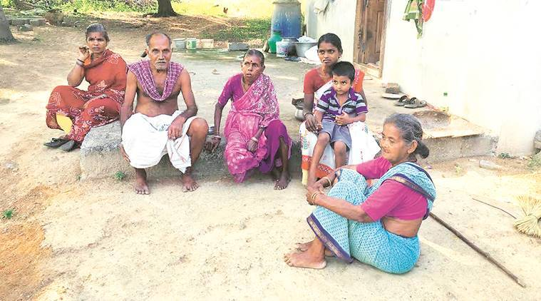 """Kavitha, with a child in her lap, says her son protests at the """"stinky"""" rice she has been forced to serve him."""
