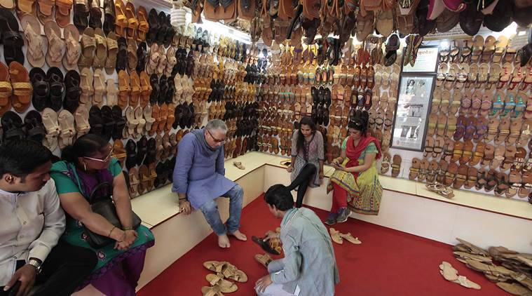 Feeling the pinch: Customers trying out slippers at a store in Kolhapur's Chappal Gali. (Source: Express photo by Pavan Khengre)