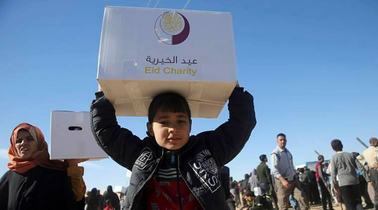 Iraqi citizens who fled the fighting between Islamic State militants and the Iraqi forces, carry boxes of aid supplies, at a camp for internally displaced people, in Khazer, east of Mosul, Iraq, Monday, Nov. 21, 2016. Iraqi troops fighting Islamic State militants in the eastern outskirts of Mosul regrouped Monday in the city's neighborhoods they recently retook from the extremist group, conducting house-to-house searches and looking for would-be suicide car bombs, a top Iraqi commander said. (AP Photo/Hussein Malla)