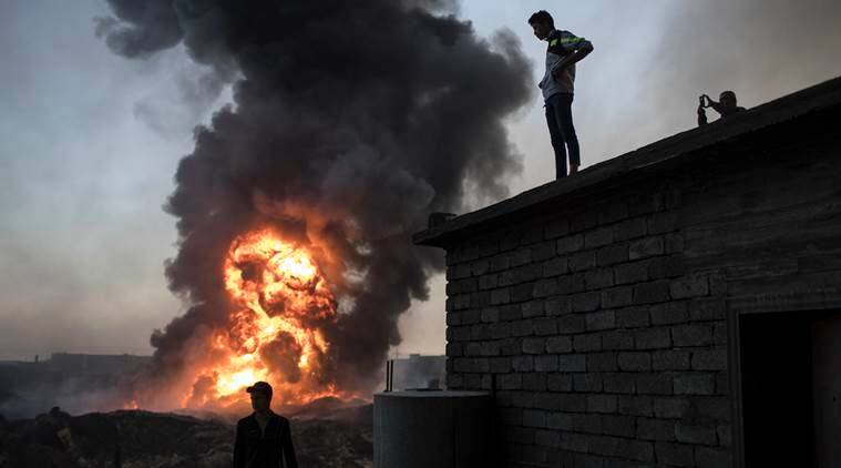 People watch as safety workers try to extinguish fires in a burning oil field in Qayara, south of Mosul, Iraq, Thursday, Nov. 3, 2016. A senior military commander says more than 5,000 civilians have been evacuated from newly-retaken eastern parts of the Islamic State group-held city of Mosul and taken to camps. (AP Photo/Felipe Dana)