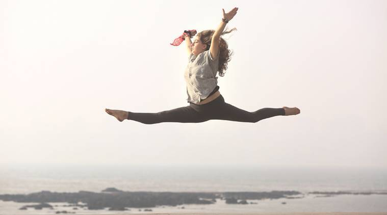 A woman shows her acrobatic skills during a hazy Tuesday evening at Marine Drive. Express Photo by Dilip Kagda