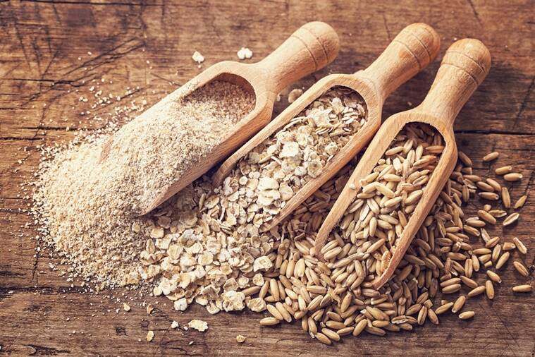 Oat flakes, seeds and bran in spoons