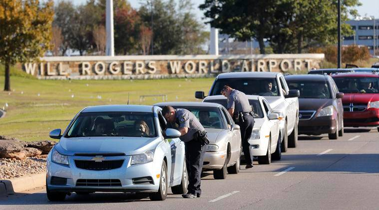 Oklahoma City police officers gather information from vehicles leaving Will Rogers World Airport, Tuesday, Nov. 15 2016, in Oklahoma City. The airport was put on lockdown after a shooting at the main terminal. (Steve Gooch/The Oklahoman via AP)