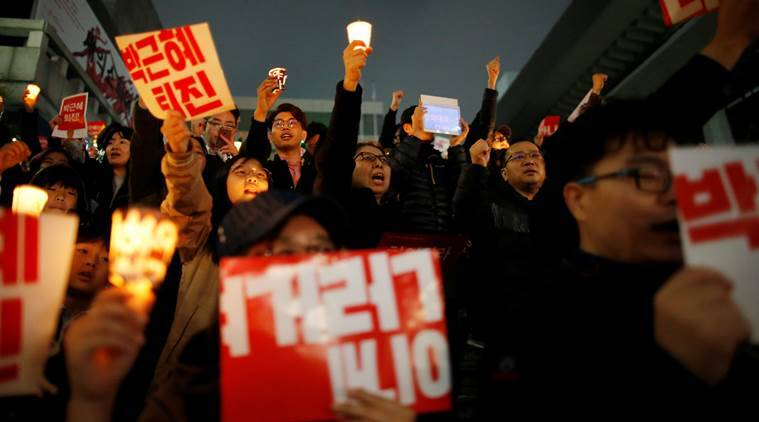 """South Korean people chant slogans during a rally calling on embattled President Park Geun-hye to resign over a growing influence-peddling scandal in central Seoul, South Korea, November 5, 2016. The placards read, """"Step down Park Geun-hye"""". REUTERS/Kim Hong-Ji"""