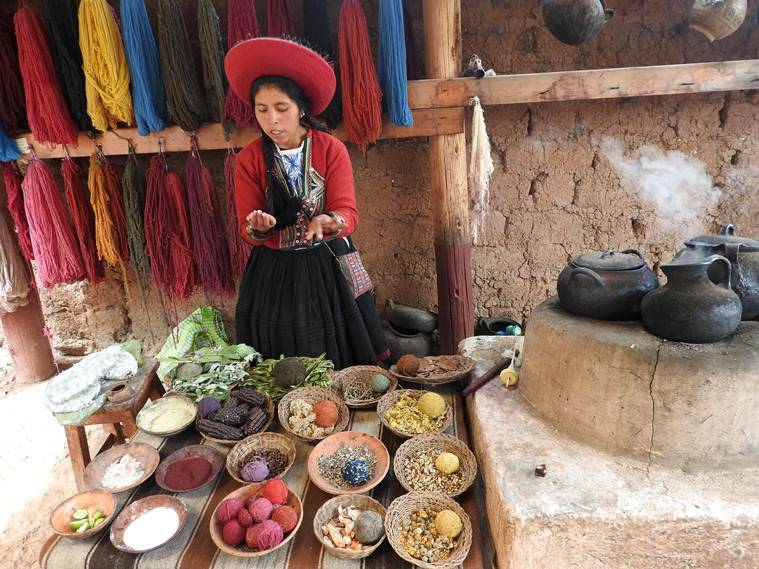 a member of the weaving  community at Chinchero sits in front of her display of yarn