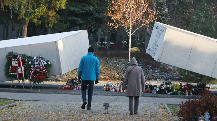 People walk towards he grave stones of some of the victims of the 2010 plane crash in Russia that killed Poland's President Lech Kaczynski and 95 other prominent Poles, at the Powazki Cemetery, in Warsaw, Poland. (AP Photo)