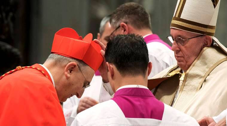 New Cardinal Mario Zenari, Apostolic Nuncio in Syria, left, receives from Pope Francis the red three-cornered biretta hat during a consistory inside the St. Peter's Basilica at the Vatican, Saturday, Nov. 19, 2016. In the ceremony to formally give the Catholic church 17 new cardinals, Francis lamented how immigrants, refugees, and those from different races or faiths are increasingly seen as enemies. (L'Osservatore Romano/pool photo via AP)