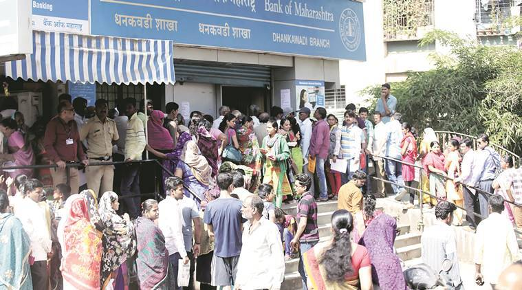 Customers wait in a long queue, to deposit, exchange and withdraw money, outside a bank.  Pavan Khengre.