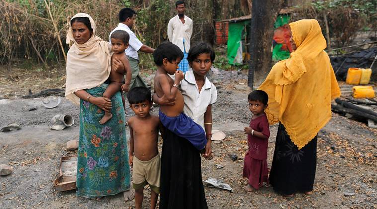 A family stands beside remains of a market which was set on fire, in Rohingya village outside Maungdaw, in Rakhine state, Myanmar October 27, 2016. Picture taken October 27, 2016.  REUTERS/Soe Zeya Tun