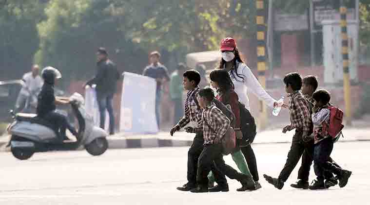Safety first: A road safety volunteer helps school students cross the road near Rajghat on Tuesday. (Source: PTI)