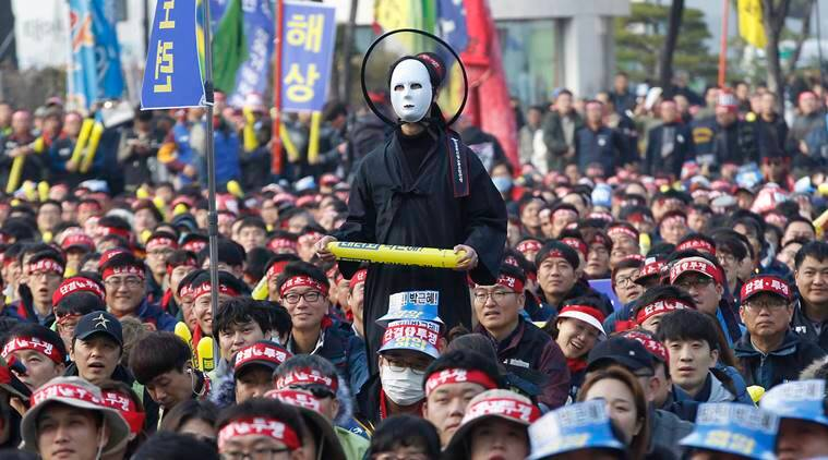 A South Korean protester wearing a mask listens to a speech during a rally calling for South Korean President Park Geun-hye to step down in Seoul, South Korea, Saturday, Nov. 19, 2016. For the fourth straight weekend, masses of South Koreans were expected to descend on major avenues in downtown Seoul demanding an end to the presidency of Park, who prosecutors plan to question soon over an explosive political scandal. (AP Photo/Ahn Young-joon)