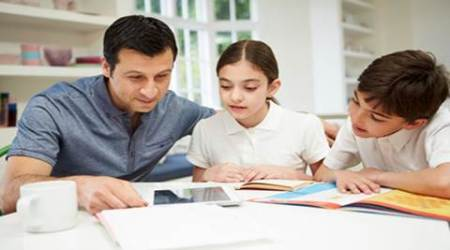 Happy Hispanic Father Helping Children With Homework Using Digital Tablet
