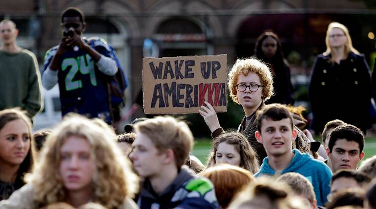 """Students look on during a walkout from classes to protest the election of Donald Trump as president, Monday, Nov. 14, 2016, in Seattle. A spokesman with Seattle Public Schools estimates that about 2,300 students from 14 middle and high schools participated in the walkout and said that students who walk out of class will get an """"unexcused absence."""" (AP Photo/Elaine Thompson)"""