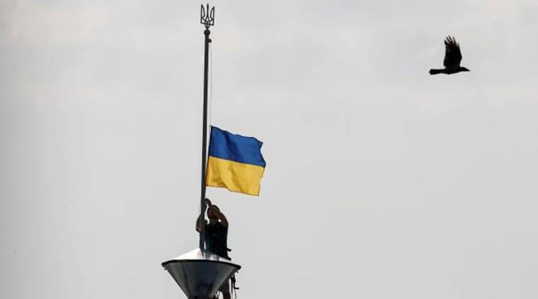 A climber installs the Ukrainian national flag on a roof, marking the Day of the State Flag, on the eve of the Independence Day, in Kiev, Ukraine, August 23, 2016. REUTERS/Gleb Garanich/File Photo