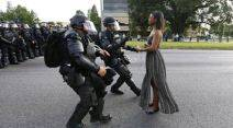 "Ieshia Evans is detained by law enforcement as she protests the shooting death of Alton Sterling near the headquarters of the Baton Rouge Police Department in Louisiana, U.S. July 9, 2016. Jonathan Bachman: 'A woman standing calmly, her long dress moving in the breeze, two police officers in full riot gear make their move. I was on assignment for Reuters in Baton Rouge to cover the protests over the fatal police shooting of Alton Sterling. Moments before I captured this image of Ieshia Evans I had my back turned photographing face-to-face confrontations between the police and the demonstrators. I heard someone behind me say something like ""don't stand there, they are arresting people in the street."" I turned and looked over my right shoulder and saw this woman standing in the road. I knew right away what was about to happen. The police were going to arrest her. I quickly moved and took the shot. When I came back to my car and looked through my take I knew I had a strong image. However I didnÕt anticipate that the image would go viral. I am grateful that it has stimulated a discussion about an important issue in this country.' REUTERS/Jonathan Bachman     TPX IMAGES OF THE DAY        SEARCH ""2016 PIX"" FOR THIS STORY. SEARCH ""THE WIDER IMAGE"" FOR ALL STORIES."