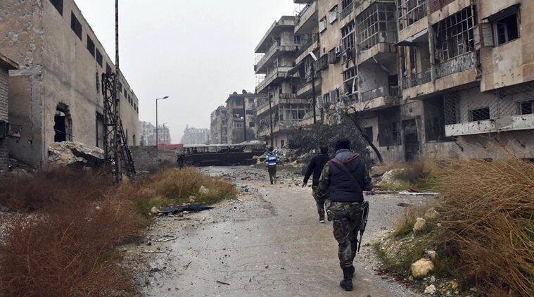 This photo released by the Syrian official news agency SANA, shows Syrian troops and pro-government gunmen marching through the streets of east Aleppo, Syria, Tuesday, Dec. 13, 2016. Syrian rebels said Tuesday that they reached a cease-fire deal with Moscow to evacuate civilians and fighters from eastern Aleppo, after the U.N. and opposition activists reported possible mass killings by government forces closing in on the rebels' last enclave. (SANA via AP)