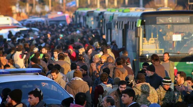 FILE - This file image released on Thursday, Dec. 15, 2016 by Aleppo 24, shows residents gathered near green government buses as they hold their belongings for evacuation from eastern Aleppo, Syria. The U.N. Security Council is expected to vote on a resolution demanding immediate and unconditional access for the United Nations and its partners to besieged parts of Aleppo and throughout Syria to ensure the delivery of humanitarian aid. (Aleppo 24 via AP, File)