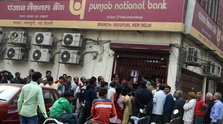 People queue up outside a bank in Mayapuri Bank. Express photo by Renuka Puri