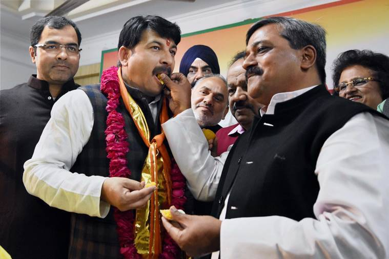 New Delhi: New BJP Delhi unit President Manoj Tiwari is offered sweets by his predecessor Satish Upadhyay after taking charge at the party office in New Delhi on Wednesday. PTI Photo by Subhav Shukla (PTI11_30_2016_000145A)