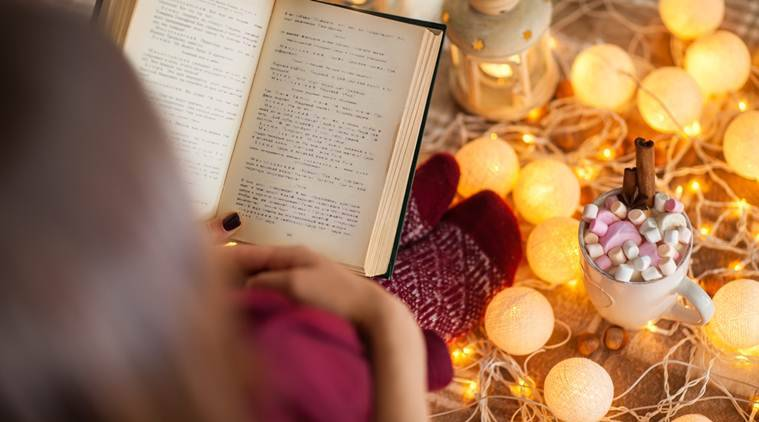 Top view of young woman at home reading book. Winter holiday concept