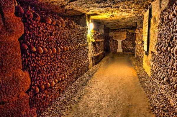 The Realm of the Dead, the Catacombs of Paris or Catacombes de Paris are underground ossuaries in Paris, France. Halls and caverns of walls of carefully arranged bones and skulls of over 6 million people.