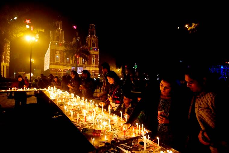 Indians light candles and offer prayers on the eve of Christmas at the Sacred Heart Cathedral in New Delhi, India, Saturday, Dec. 24, 2016. Though the Hindus and Muslims comprise majority of the population in India, Christmas is a national holiday celebrated with much fanfare. (AP Photo/Manish Swarup)