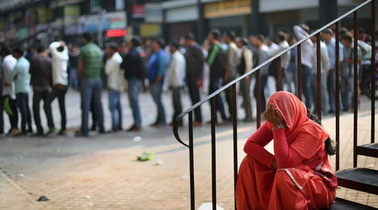 A woman takes rest next to a queue outside an ATM in Nehru Place, New Delhi. (Source: Express photo by Oinam Anand)