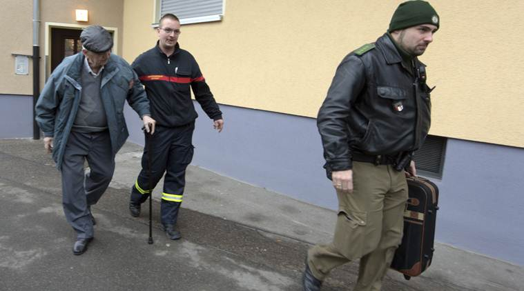 Police help a man to leave his apartment in Augsburg, Germany, Sunday Dec. 25, 2016. Thousands of people in the German town of Augsburg have temporarily left Christmas presents and decorations behind while authorities disarm a World War II bomb. The bomb was uncovered last week during construction work. (Stefan Puchner/dpa via AP)