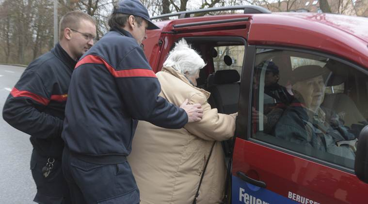 Rescuers help a woman into a car of the fure brigade after she left her home in Augsburg, Germany, Sunday, Dec. 25, 2016. Thousands of people in the German town of Augsburg have temporarily left Christmas presents and decorations behind while authorities disarm a World War II bomb. The bomb was uncovered last week during construction work. (Stefan Puchner/dpa via AP)