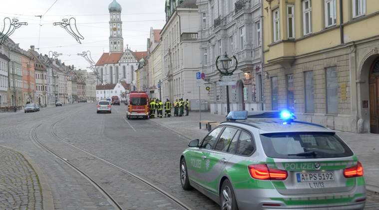 A police vehicle driving through an almost empty street in Augsburg, Germany, Sunday Dec. 25, 2016. Thousands of people in the German town of Augsburg have temporarily left Christmas presents and decorations behind while authorities disarm a World War II bomb. The bomb was uncovered last week during construction work. (Stefan Puchner/dpa via AP)