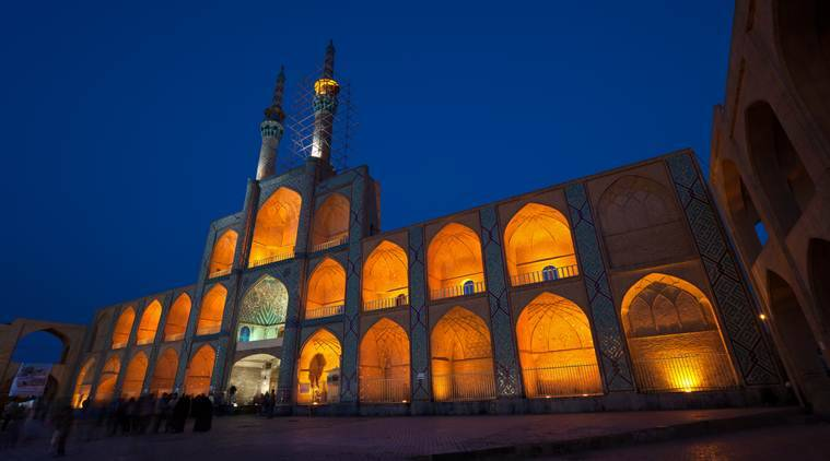 Facade of illuminated Amir Chakhmaq mosque situated in a square with similar name, against dark blue sky in the city of Yazd.